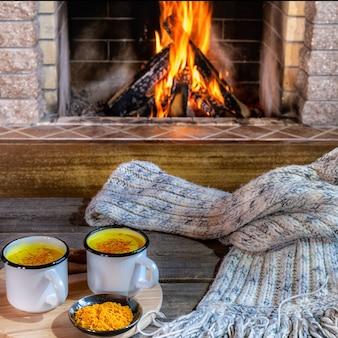 居心地の良い暖炉の前にターメリックとスパイスが入ったマグカップの黄金ラテミルク。健康飲料。