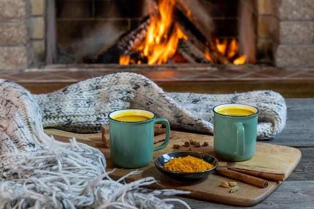 居心地の良い暖炉の前でターメリックとスパイスで作られた黄金のラテミルク。健康なコロナウイルス保護ドリンク。