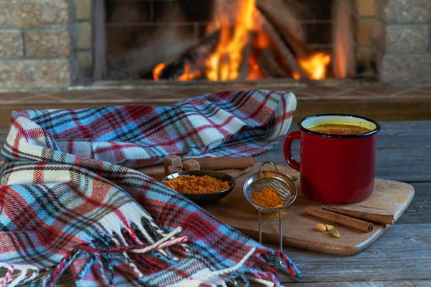 Golden latte milk made with turmeric and spices before cozy fireplace. healthy coronavirus protection beverage.
