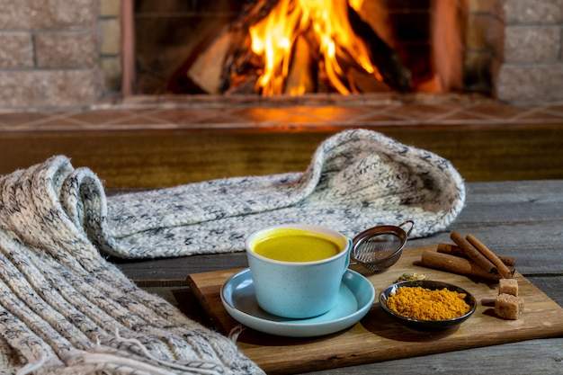 Golden latte milk made with turmeric and spices before cozy fireplace. healthy coronavirus protection drink.