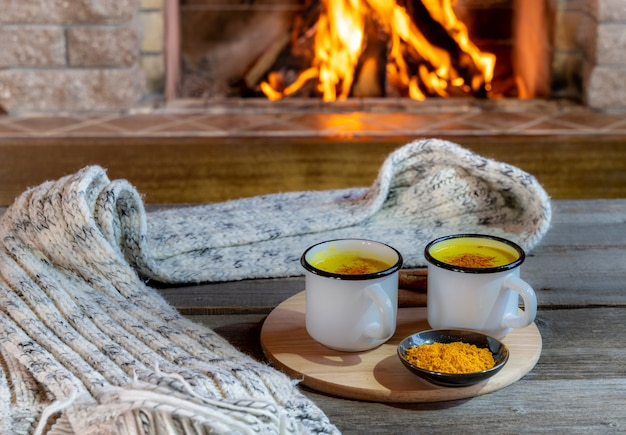 Golden latte milk made with turmeric and spices before cozy fireplace.