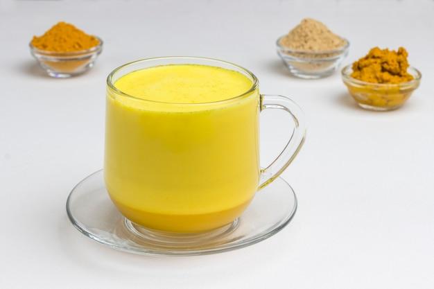 料理の材料が入ったゴールデンラテ。ガラスのインドのターメリックゴールデンミルク。
