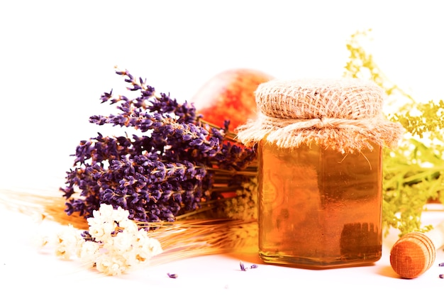 Golden lavender honey in a glass jar with dry herbs on light background.