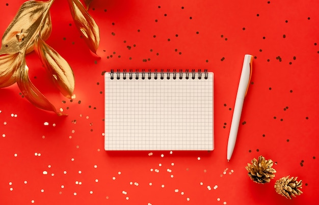 Golden leaf and notebook isolated on red