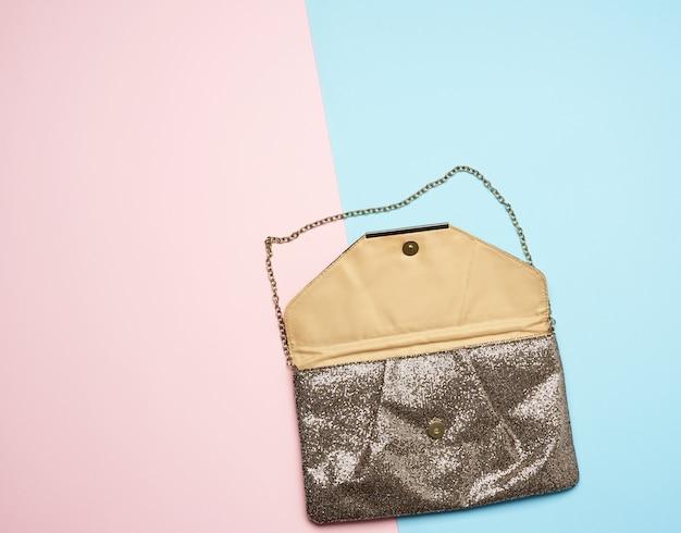 Золотой кожаный модный клатч на металлической цепочке на цветном фоне