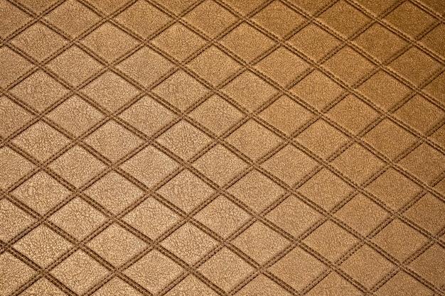 ソファまたは茶色の布と空白の木製の壁に金色の革の質感