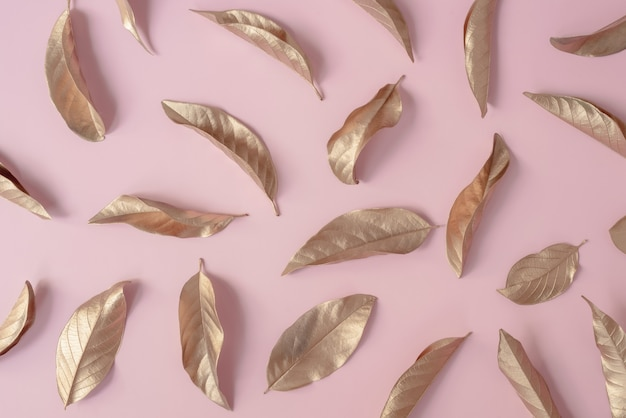 Golden leaves on a pink background