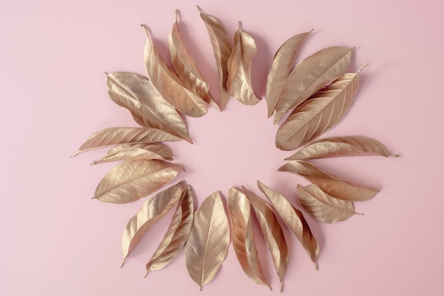 Golden leaves placed in a circle frame on a pink background