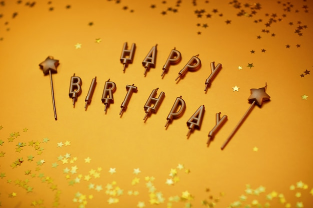 Golden letters happy birthday on a gold background with stars.