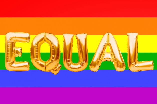 Golden letters made from balloons forming word equal on pride rainbow flag background