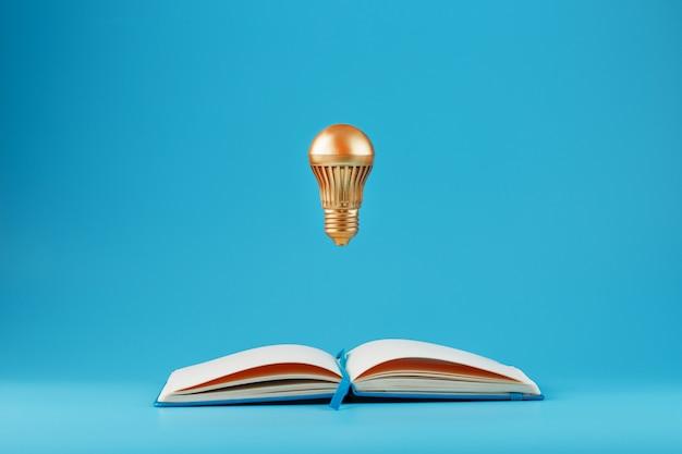 A golden light bulb in levitation from an open notebook on blue.
