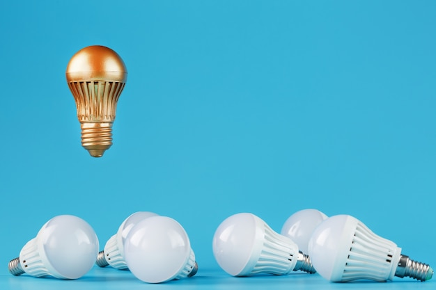 The golden light bulb rises and hovers above the surroundings of ordinary light bulbs.