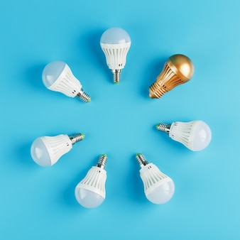 A golden light bulb stands out in the circle of light bulbs of a ring of white lamps on a blue wall.