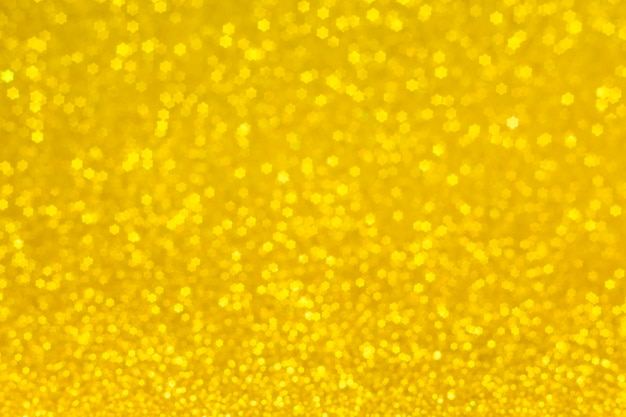 Golden lights in the shape of stars for a festive background. abstract, bright yellow background, blurred bokeh.