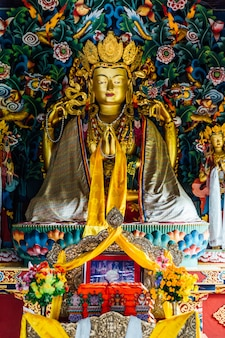Golden lord buddha statue in bhutanese style inside the royal bhutanese monastery in bodh gaya, bihar, india.