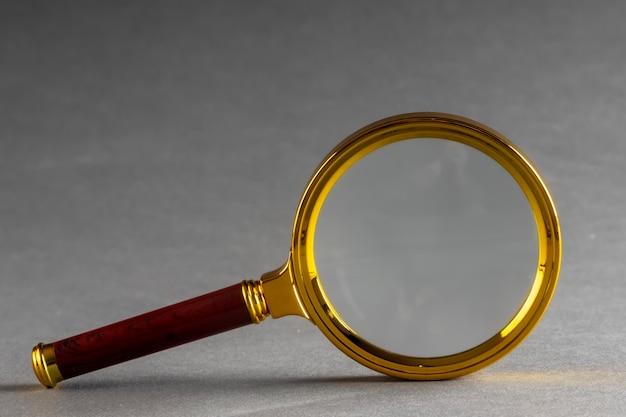 A golden magnifier on black paper surface