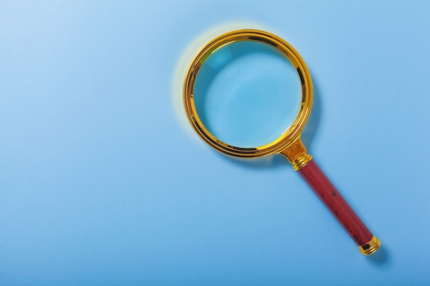 Golden magnifier on blue paper