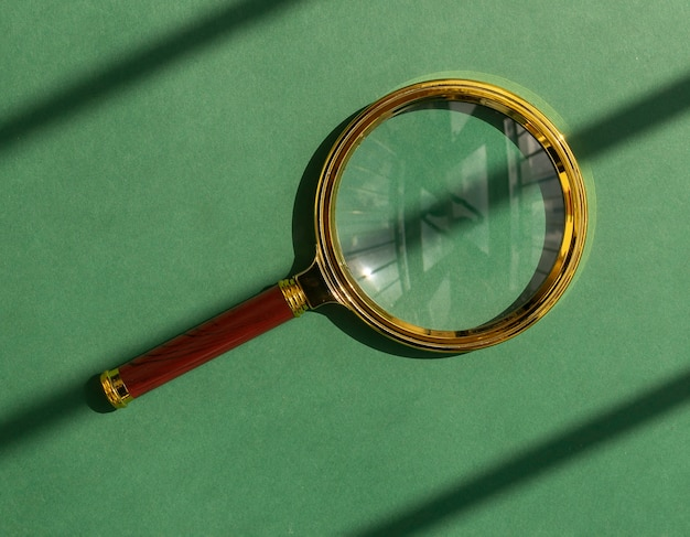 Golden magnifying glass over eco green background with beautiful sunny light magnifier as concept of...