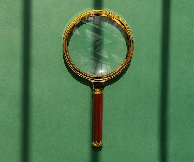 Golden magnifying glass over green shadowstriped background magnifier as concept of finding answers