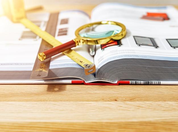 나무 책상에 열려 있는 두꺼운 기술 책 위에 있는 황금 돋보기는 과학의 개념을 닫습니다...
