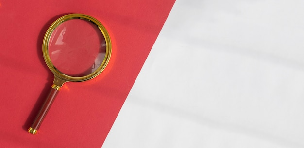 일 빛으로 빨간색과 흰색 배경 위에 황금 돋보기. 검색 도구 개념. copyspace와 배너입니다.