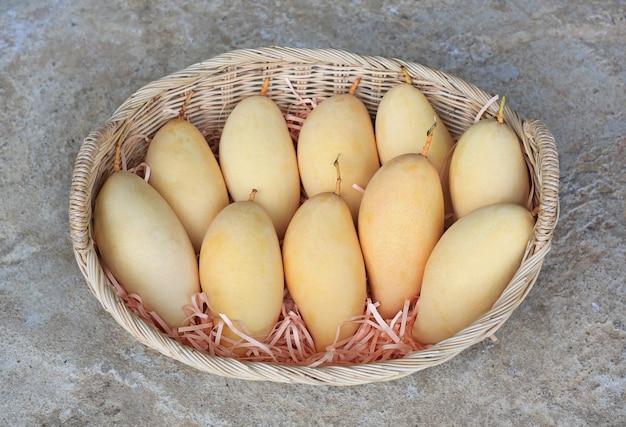 ゴールデンマンゴーフルーツ籐かご。熟した黄色のバラクーダマンゴー。タイのトロピカルフルーツ。