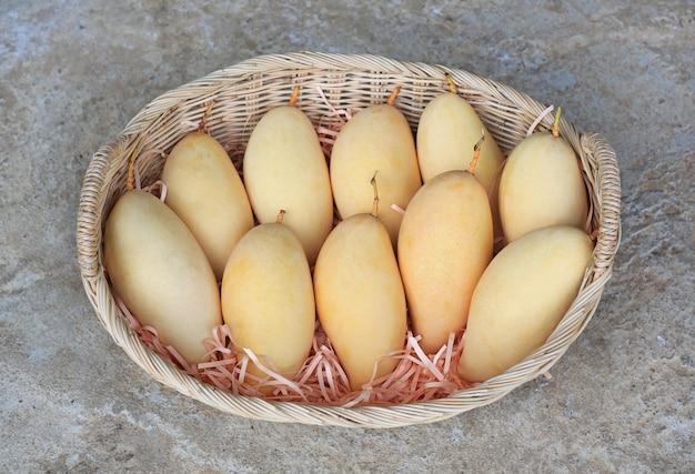 Golden mangoes fruit in rattan basket. ripe yellow barracuda mango. tropical fruit in thailand.
