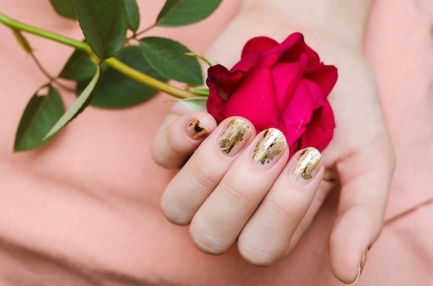 Golden manicure. female hand holding red rose.
