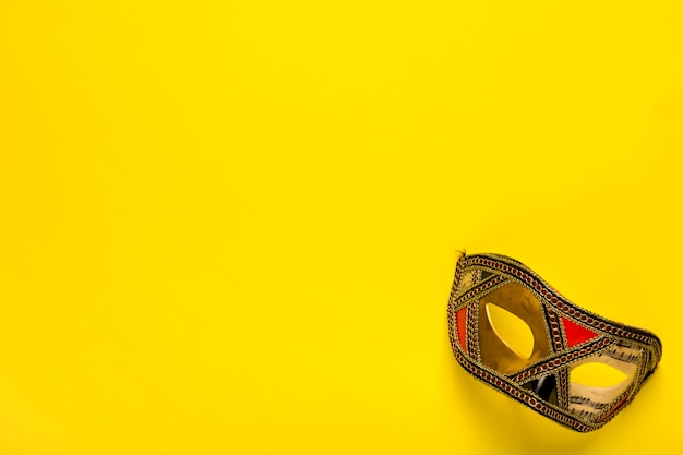 Golden mask on yellow background with copy space