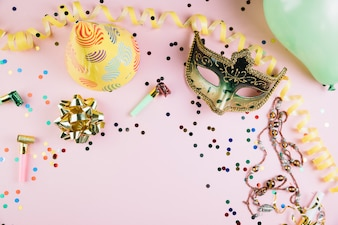 Golden masquerade carnival mask with party decorations on pink backdrop