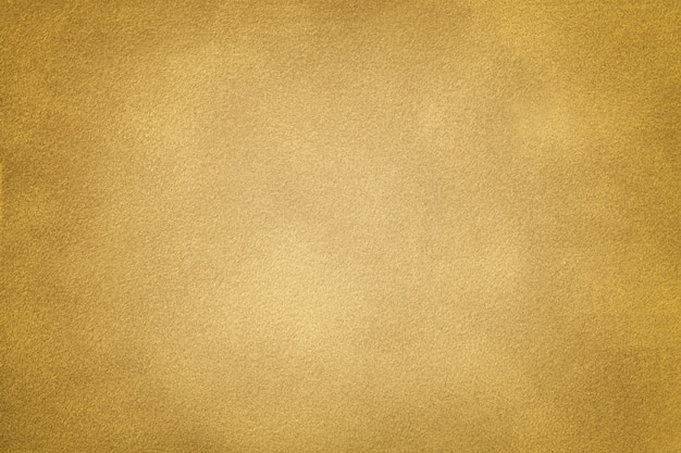 Golden matt suede fabric closeup. velvet texture background