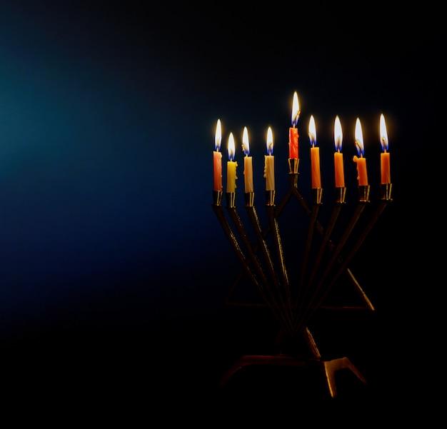 Golden menorah lighted candles on menorah for the jewish holiday hanukkah.