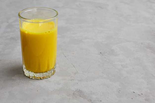 Golden milk in a glass with turmeric and honey additives.