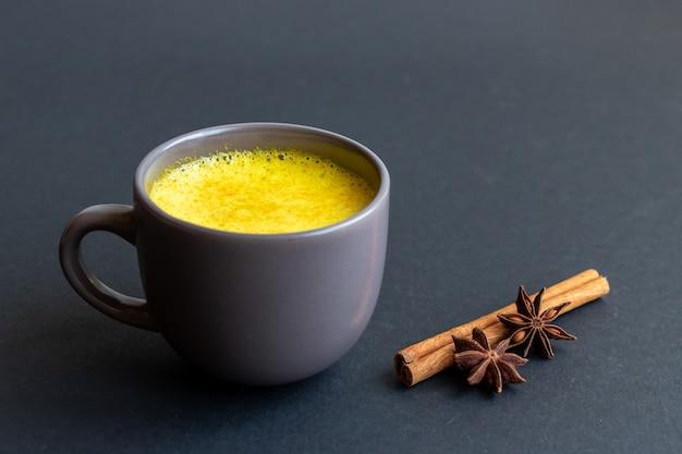 Golden milk in a gray cup on dark