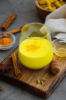 Золотое молоко в стакане на деревянной доске с медом и другими специями. полезный напиток из молока и куркумы.