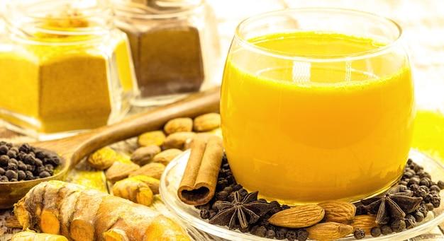 ターメリックや他のスパイスで作られたゴールデンミルク、健康的なサフランドリンク、シナモン、スターアニス、黒コショウ、アーモンド