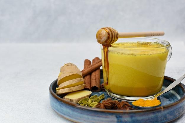 Golden milk or turmeric latte with curcuma powder ayurvedic drink