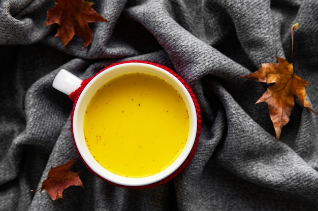 Golden milk in a white cup. autumn leaves. a healthy drink made from milk, turmeric, cinnamon and honey.