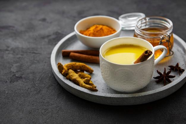 Золотое молоко с корицей, куркумой, имбирем и медом на черной бетонной поверхности