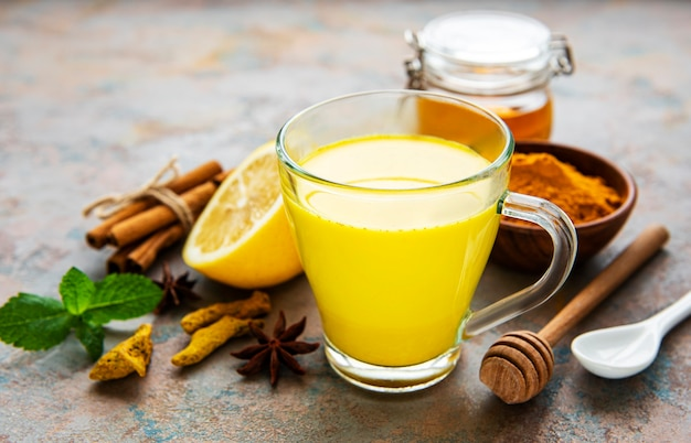 Golden milk with cinnamon, turmeric, ginger  and honey over concrete surface