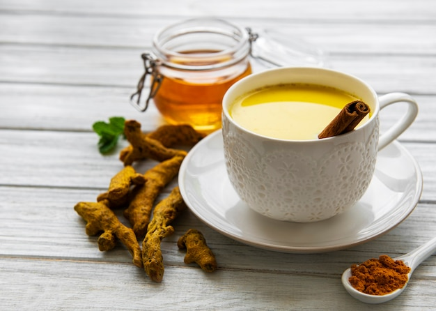 Golden milk with cinnamon, turmeric, ginger  and honey over white wooden surface