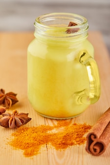 Golden milk with turmeric, cinnamon sticks, turmeric and anise on a wooden surface