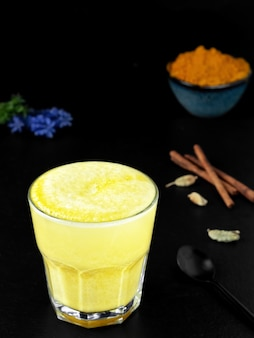 Golden milk with turmeric and other spices on a black surface