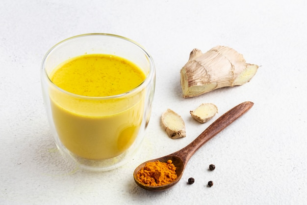 Golden milk with turmeric powder in glass over white background