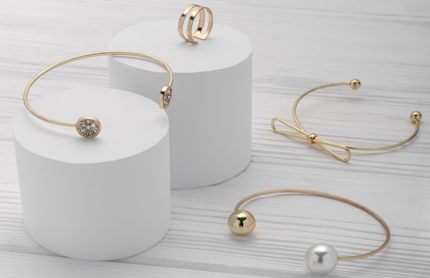 Golden modern bracelets collection and ring on white platforms on wooden background
