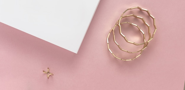 Golden modern bracelets and ring on white and pink