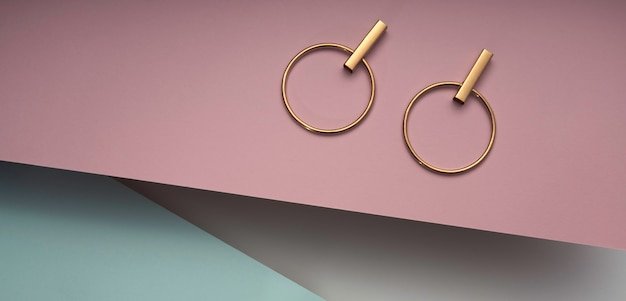 Golden modern earring pair on pink and blue background. circle modern design golden earrings on pastel colors background