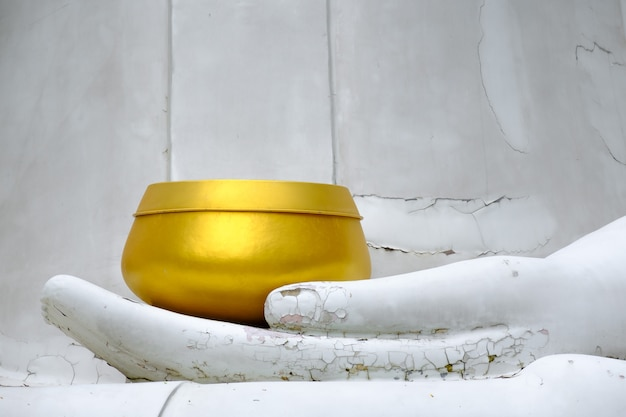 Golden monk's alms bowl on cracked hand statue