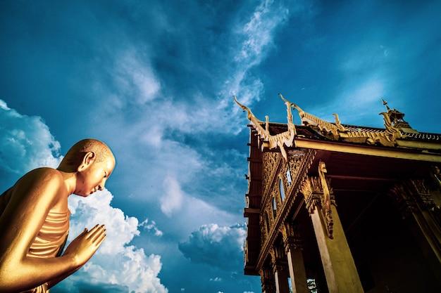 Статуя золотого монаха и храм, таиланд молится. золотой стоящий монах сжимает руки вместе на груди или лбу в знак уважения