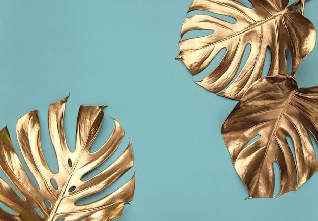 Golden monstera leaves on light turquoise background
